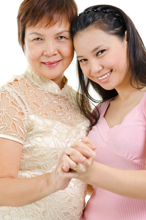 Mixed race beautiful Asian family portrait. Elderly mother and adult daughter holding hands bonding isolated on white . photo