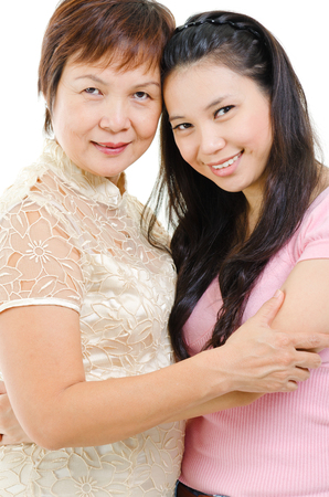 Senior mother and adult daughter holding hands bonding isolated on white . Mixed race Asian family portrait.  photo