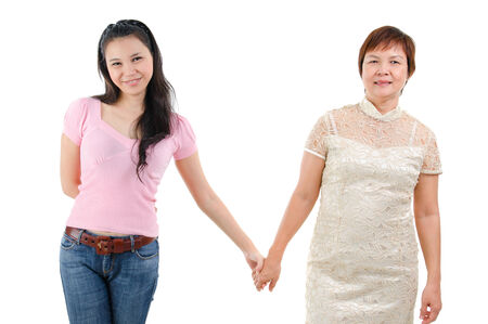 Adult daughter holding hands with mother isolated on white . Mixed race Asian family portrait. Stock Photo