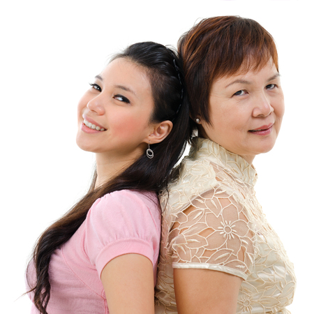 pan asian: Adult daughter back to back with mother isolated on white background. Mixed race Asian family portrait.