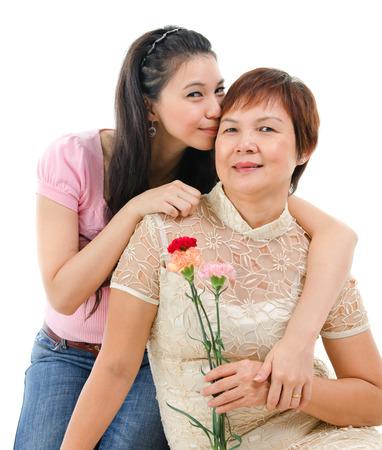 mom daughter: Senior madre sosteniendo la flor del clavel, hija adulta abraza y los besos mamá, aislado en fondo blanco. Raza mixta retrato de familia asiática.