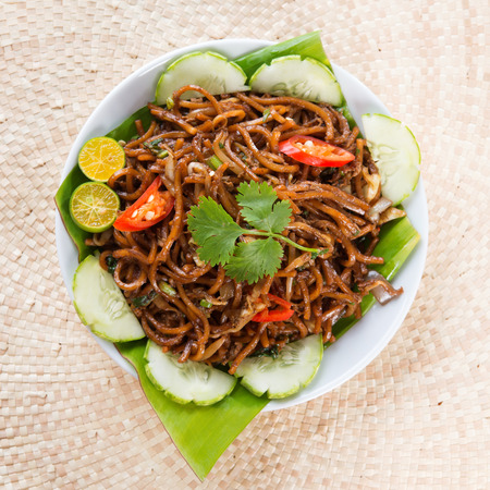 Asian food spicy fried noodles, ready to serve on dining table. photo