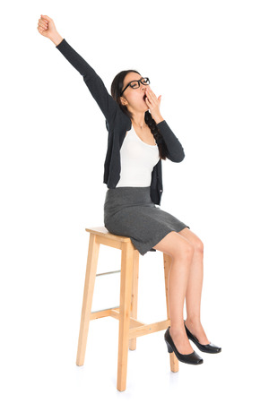 yawning: Full body Asian business woman yawning, seated on chair isolated white .