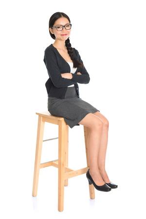 stool: Full body Asian business woman seated on chair, arms crossed isolated on white . Chinese girl model. Stock Photo