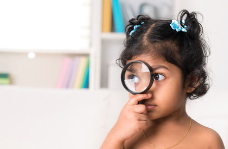 Child at home. Cute Indian girl peeking through magnifying glass. photo