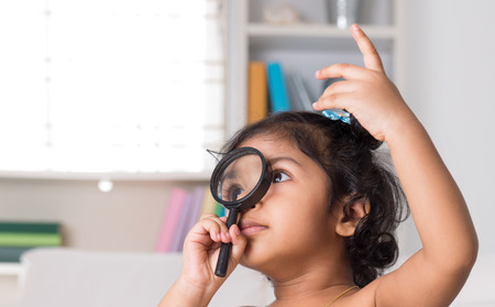 Cute Indian girl peeking through magnifying glass. Asian child at home. photo