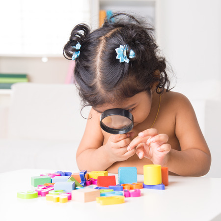 A little Indian girl zoom into toys through a magnifying glass, living lifestyle at home. photo
