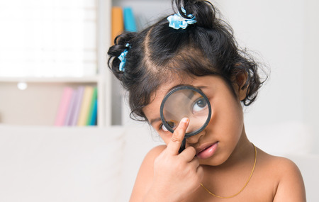A little Indian girl peers at the camera through a magnifying glass, living lifestyle at home. photo