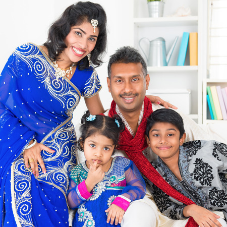 Portrait of Asian Indian family at home, happy parents and children in traditional sari.