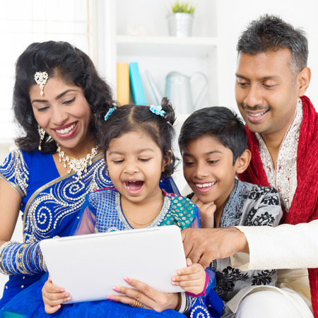 Indian family using digital computer tablet at home. Asian family living lifestyle. photo
