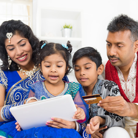 Indian Asian family using digital tablet pc computer online shopping with credit card at home. India family living lifestyle. Happy smiling parents and children. photo