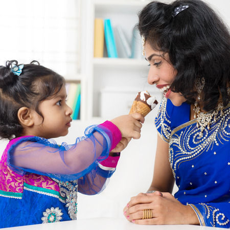 india food: Indian girl feeding her mum ice-cream. Asian family living lifestyle at home.