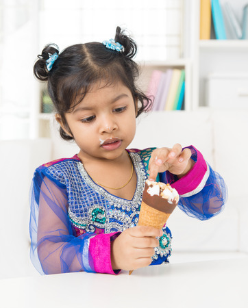 Eating ice cream. Indian Asian girl enjoying an ice cream at home. photo
