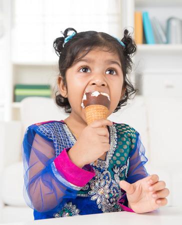 Eating ice cream. Cute Indian Asian girl enjoying an ice cream. Beautiful child model at home. photo