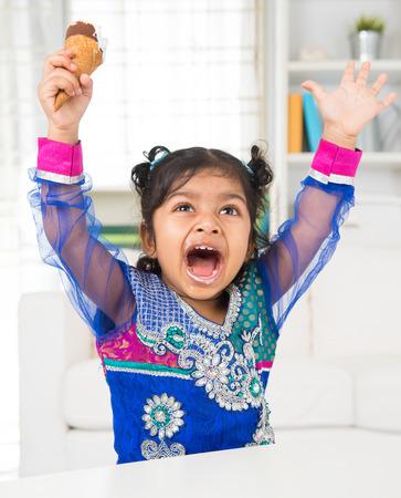 Eating ice cream. Cheerful Indian Asian girl enjoying an ice cream. Beautiful child model at home. photo