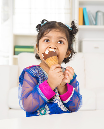 Eating ice cream. Indian Asian girl enjoying an ice cream. Beautiful child model at home. photo