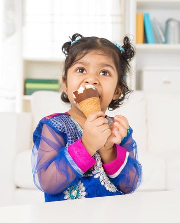 Eating ice cream. Indian Asian girl enjoying an ice cream. Beautiful child model at home. photo