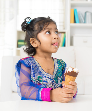 Little Indian girl licking her lips with an ice cream cone in hand, family living lifestyle at home. photo