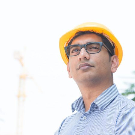 Portrait of an Asian Indian engineer looking away, standing in front construction crane, inspecting the progress of project. photo