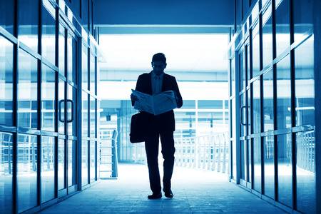 moving office: Silhouette of business man residing newspaper and walking thru modern office building, in blue tone.