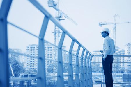 Aziatische Indiase architect bezoeken van bouwmaterieel, het inspecteren van de voortgang.