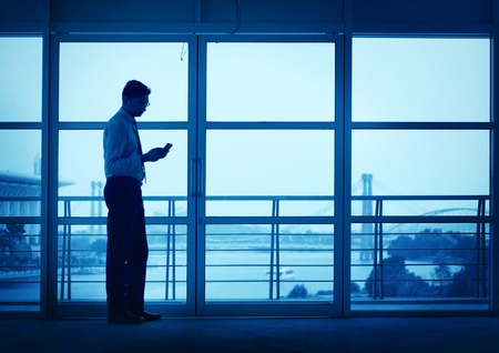 businessman waiting call: Silhouette of Asian Indian man using mobile phone in modern office building, blue tone.