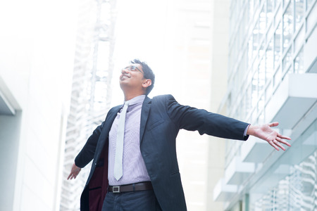 Indian businessman open his arms wide, looking up into the light, modern office building as background, natural sunlight. photo