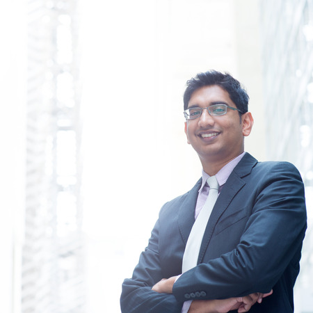 Portrait of a good looking smiling Indian businessman crossed arms standing at modern building, with natural light. photo