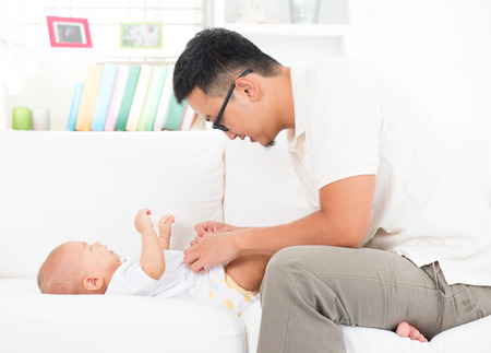 changing clothes: Joven padre de cambiar los pa�ales y la ropa para el beb�. El estilo de vida de la familia asi�tica en casa.