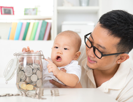 ahorros: El estilo de vida de la familia asiática en casa. Padre e hijo ahorrando monedas para frasco de dinero, la planificación financiera concepto.
