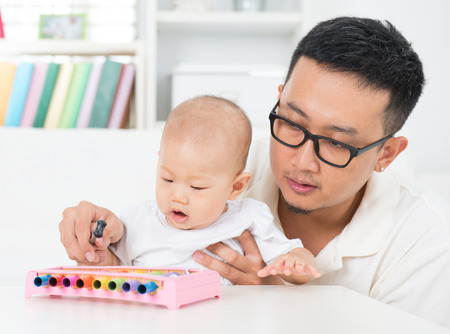 Asian family lifestyle at home. Father playing music instrument with baby. Sound development concept.