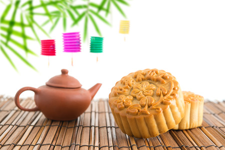 mid autumn: Chinese mid autumn festival foods with blank copy space. Traditional mooncakes on table setting with teacup. The Chinese words on the mooncakes means assorted fruits nuts, not a logo or trademark.