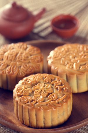 Retro vintage style Chinese mid autumn festival foods. The Chinese words on the mooncakes means assorted fruits nuts, not a logo or trademark. Traditional mooncakes on table setting with teacup.  photo