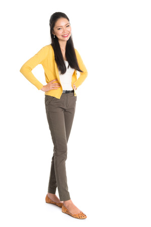 yellow shirt: Portrait of an Asian girl smiling happy, full length standing isolated on white background. Stock Photo