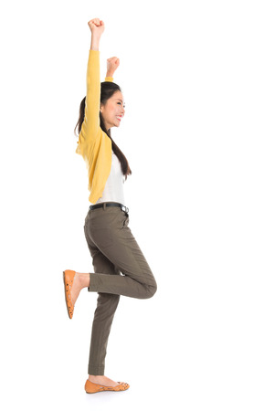 Side view or profile of an Asian girl arms up happy jumping around, full length standing isolated on white .