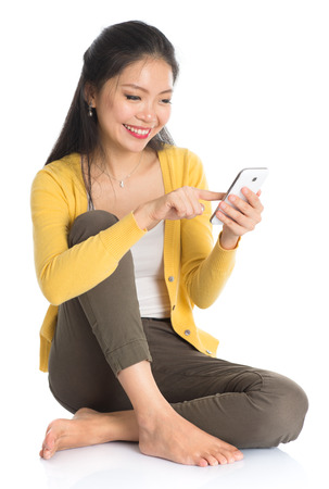 Full body Asian girl in yellow blouse texting with smartphone, seated on floor isolated on white . photo