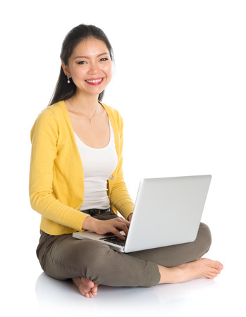 Full body Asian woman in yellow blouse using laptop computer notebook, looking at camera, seated on floor isolated on white . photo