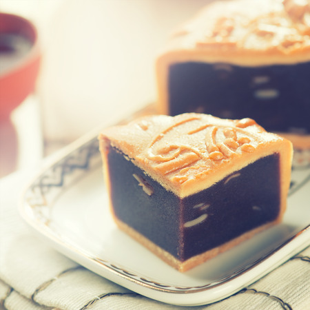 Traditional red beans paste mooncakes on white plate with teacup. Chinese mid autumn festival foods.  photo