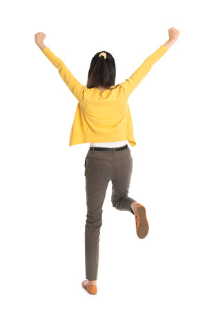woman dancing: Rear view or back of an Asian girl arms up happy jumping around, full length standing isolated on white . Stock Photo
