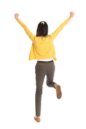 donna che balla: Vista posteriore o posteriore di una ragazza asiatica braccia fino felici saltare, piena lunghezza in piedi isolato su bianco.