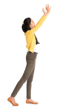 Vista lateral o perfil de una chica asiática brazos hacia arriba como empujar algo lejos, de cuerpo entero de pie aislado en blanco.