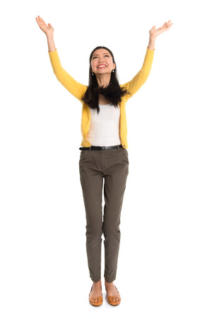 Asian girl arms up, looking upwards like holding something above, full length standing isolated on white . photo