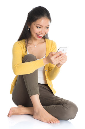 Full body Asian woman in yellow blouse texting with smartphone, seated on floor, isolated on white  photo