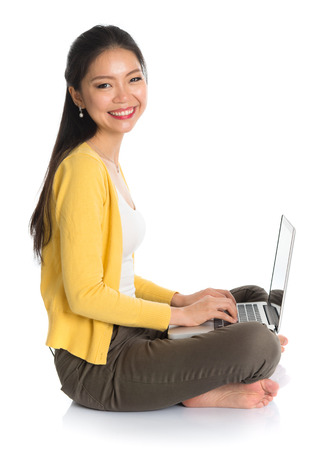 Side view full body Asian woman in yellow blouse using laptop computer notebook, looking at camera, seated on floor isolated on white . photo