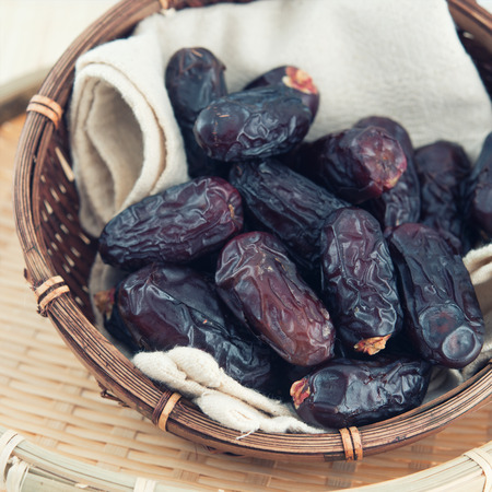 date palm tree: Dates fruit or kurma. Pile of fresh dried date fruits in a basket. Stock Photo