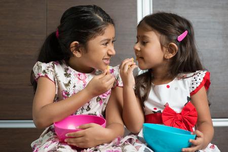 murukku: Two cute Indian girls eating murukku. Asian sibling or children living lifestyle at home. Stock Photo