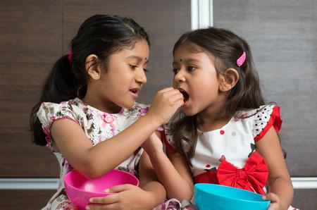 fille indienne: Les filles indiennes partage de la nourriture, murukku uns avec les autres. Frère asiatique ou le mode de vie des enfants vivant à la maison.