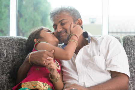 Happy Indian family at home. Asian sweet daughter kissing her father face indoor, sitting on sofa. photo
