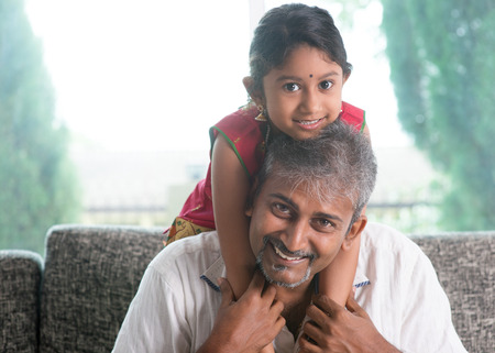 familia abrazo: Familia india feliz en el pa�s. Padre asi�tico cuestas su hija, sentado en el sof�. Padres y estilo de vida interior del ni�o. Foto de archivo