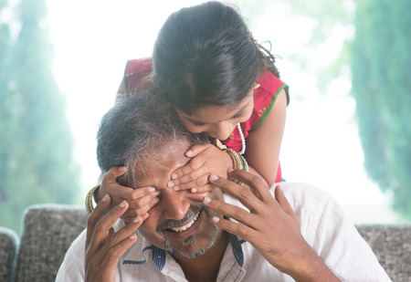 hands covering face: Happy Indian family at home. Asian girl surprising her father by covering daddy eyes. Parent and child indoor lifestyle.